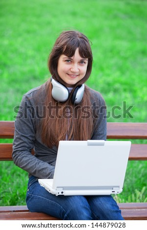 Brunette girl sitting at the bench with notebook