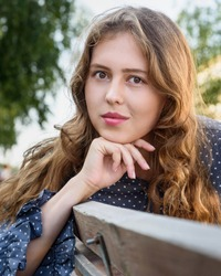 Brunette girl sitting on bench in the city. Portrait of girl in blue dress with long hair on the street in summer day