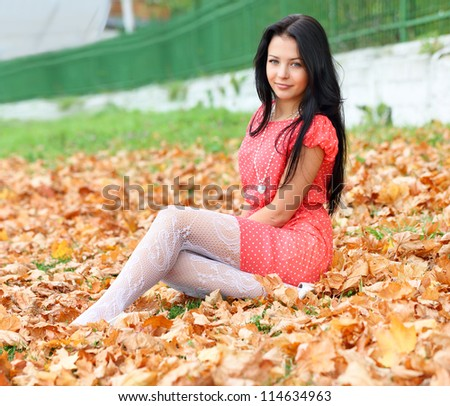 brunette girl sitting on the autumn leaves
