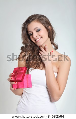 Brunette girl smiling with a red box