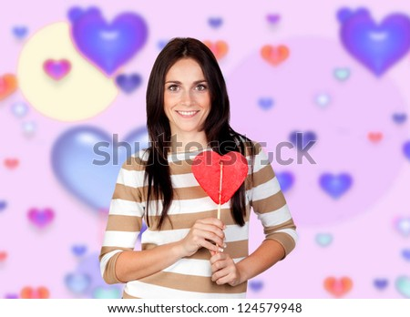 Brunette girl with a big lollipop and a background of colorful hearts