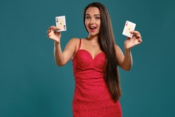 Brunette girl with a long hair, wearing a sexy red dress is posing holding two playing cards in her hands, blue background.