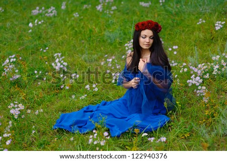 brunette girl with a wreath on his head against the green grass