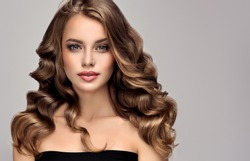 Brunette  girl with long  and   shiny curly hair .  Beautiful  model woman  with curly hairstyle   .Care and beauty of hair