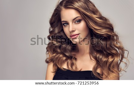 Brunette  girl with long  and   shiny curly hair .  Beautiful  model woman  with curly hairstyle. Care and beauty of hair
