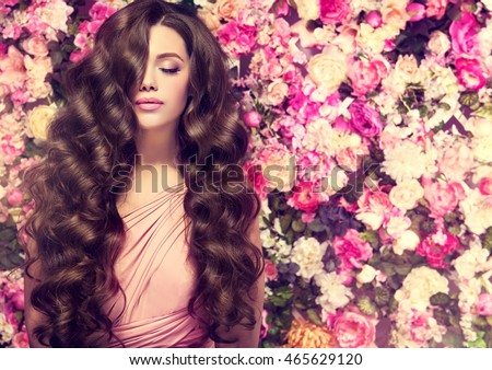 Brunette  girl with long  and   shiny wavy hair .  Beautiful  mode woman with curly hairstyle ,   background  wall of flowers .