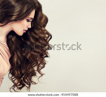 Brunette  girl with long  and   shiny wavy hair .  Beautiful  model with curly hairstyle #454497088