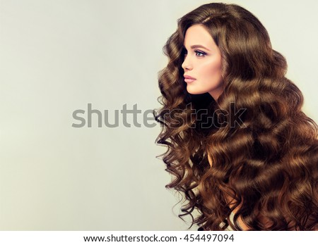 Brunette  girl with long  and   shiny wavy hair .  Beautiful  model with curly hairstyle