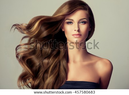 Stock Photo Brunette  girl with long  and   shiny wavy hair .  Beautiful  model with curly hairstyle .