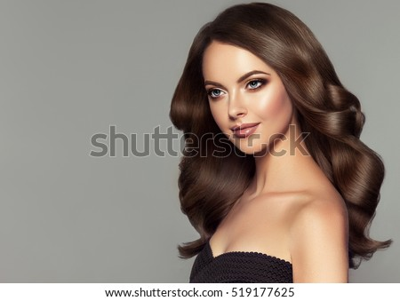 Brunette girl with long and shiny wavy hair. Beautiful model with curly hairstyle.