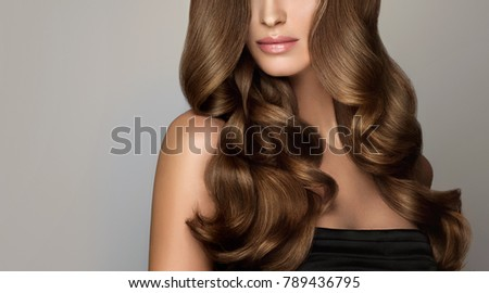 Brunette  girl with long  and   shiny wavy hair .  Beautiful  model woman with curly hairstyle . #789436795