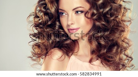Brunette  girl with long  and  volume shiny wavy hair .  Beautiful  model with curly hairstyle .