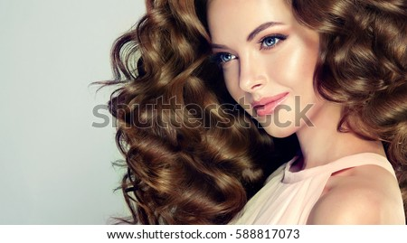 Stock Photo Brunette  girl with long  and  volume shiny wavy hair .  Beautiful  model with curly hairstyle .