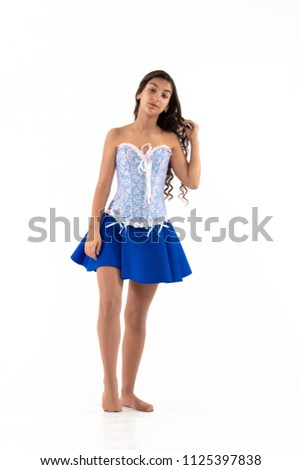 Stock Photo brunette girl with long hair in blue corset and short skirt posing on white background