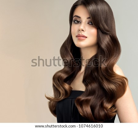 Brunette  girl with long , healthy and   shiny curly hair .  Beautiful  model woman  with wavy hairstyle   .Care and beauty