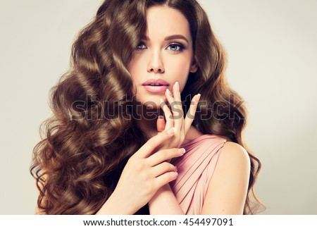 Stock Photo Brunette  girl with long  , shiny wavy hair .  Beautiful  model with curly hairstyle . Woman with beautiful hands  french manicure