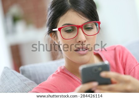 Brunette girl with red eyeglasses reading message on smartphone
