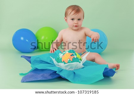 Brunette hair blue eyed baby boy holding hand up and sitting in front of his blue yellow green and orange giant fishy birthday cupcake with tissue paper on a seamless green background with balloons