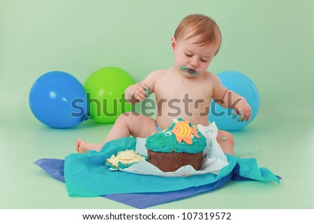 Brunette hair blue eyed baby boy with icing on face looking down at his smashed fish themed birthday cake with orange fish while sitting on green seamless background with green and blue balloons him