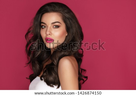 Brunette haired Woman Portrait with brown eyes and Healthy Long Shiny Wavy hairstyle. Volume shampoo. Black Curly permed Hair and bright makeup.  Beauty salon and haircare concept.