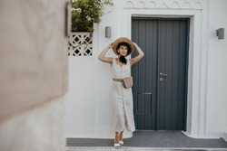 Brunette happy woman in stylish hat and white summer dress poses outside. Lady in boater and stylish outfit stands near grey wooden door and white building.