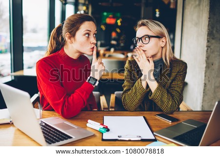Brunette hipster blogger told secret to wondered colleague and showing sign shh during collaborating at laptop devices in coworking.Excited two best friends gossiping during studying break at netbooks