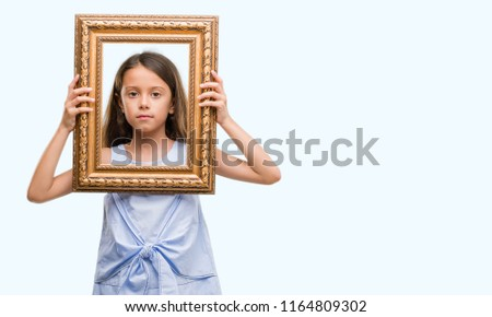 Brunette hispanic girl holding vintage art frame with a confident expression on smart face thinking serious