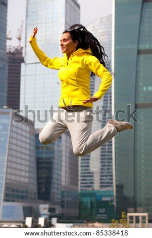 brunette in a yellow blazer jumping on the background the skyscrapers of a big city