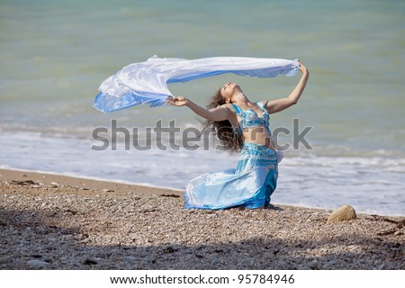 Brunette in costume for belly-dance is dancing on the beach. Girl is dancing outdoors