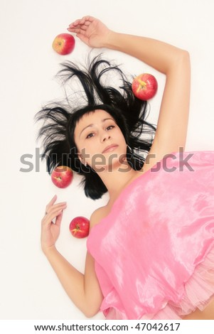 Brunette in pink with flying apples on white background.