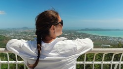 brunette in sunglasses admires pictorial tropical cityscape and ocean bay on observation deck under blue sky backside view