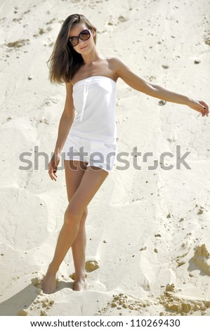 Brunette in white dress against a background of sand