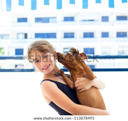 Brunette kid girl with summer swimsuit playing with dog in apartment