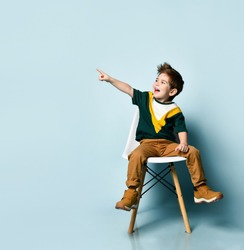 brunette kid in colorful t-shirt and brown pants. Smiling and pointing at something by forefinger, sitting on white chair against blue studio background. Childhood, fashion. Close up, copy space