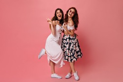 Brunette lady shows peace sign and poses with her friend on pink background. Girls with wavy hair in white fashionable dresses and converse hugging