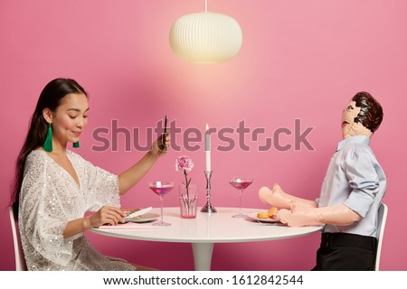 Brunette lady tries to find true love or sweetheart online on internet, takes selfie on smartphone, sits at dinner table with layman doll, prepares for first date with stranger in real life.