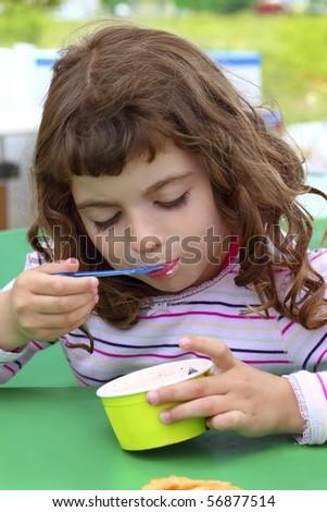 brunette little girl eating summer ice cream color spoon