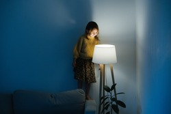 Brunette little girl in yellow knitted sweater and leopard skirt standing on a backseat of a couch at home. She's looking at dim night light from above. Her face is lit.