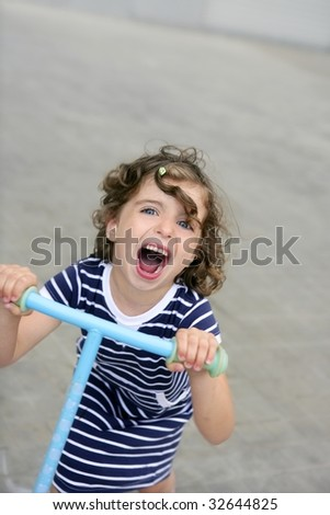 Brunette little girl with scooter in gray city background