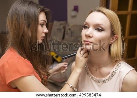 Brunette make up artist woman applying make up for a blonde bride in her wedding day. Making tone correction #499585474