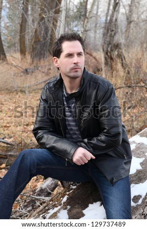 Brunette male model outdoors wearing leather jacket and jeans