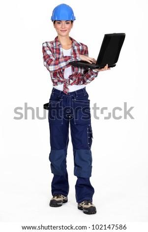 Brunette manual worker holding laptop