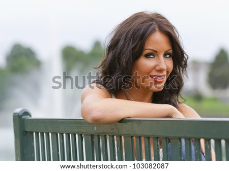 Brunette model sitting in a park near a pond