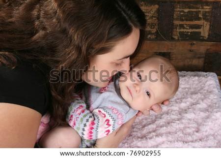 Brunette mother lovingly holding her baby girl