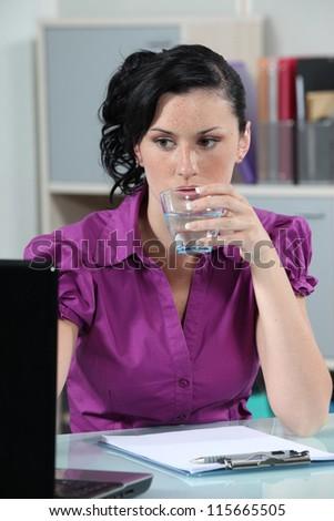 Brunette office worker drinking glass of water