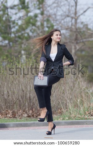 Brunette on stiletto heels in the park. Happy young woman in black suit with tablet computer in her hands runs along the park
