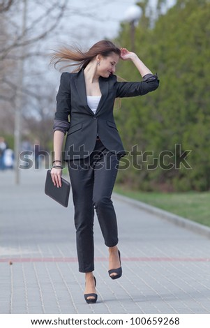 Brunette on stiletto heels in the park. Young woman in black suit with tablet computer in her hands walks along the park
