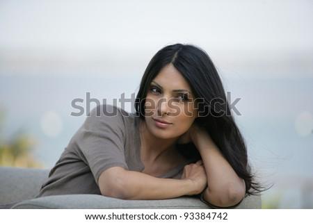 Brunette sat outdoors on sofa