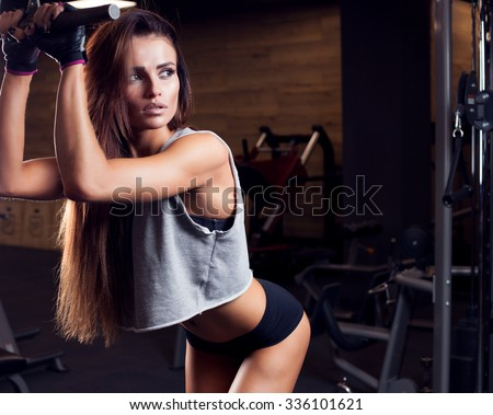 Stock Photo Brunette sexy fitness girl in sport wear with perfect body in the gym posing before training set