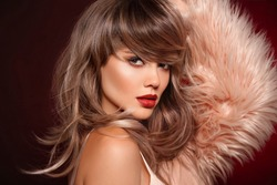 Brunette short hairstyle. Red lips makeup. Beautiful Woman in fur coat. Gorgeous model with short shiny haircut. Concept Coloring Hair. Beauty Salon.